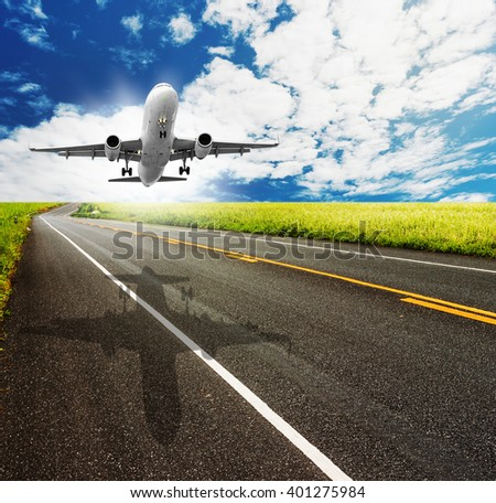 asphalt road through the green field and airplane on blue sky in summer day - stock photo