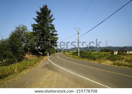 asphalt road through the green field and clouds on blue sky - stock photo