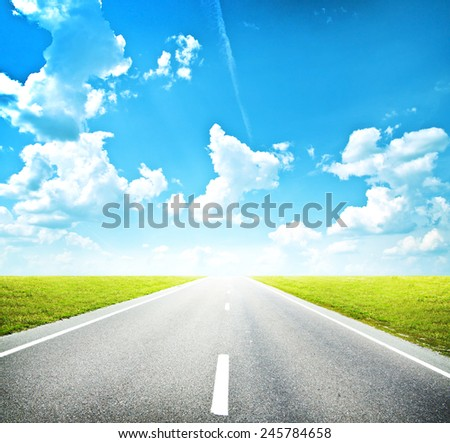 Asphalt road through the green field and clouds on blue sky in summer day