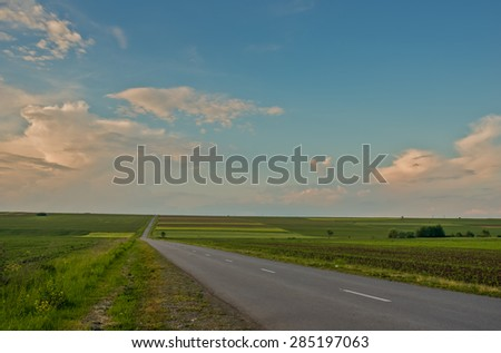 Asphalt road through the green field and clouds on blue sky in the evening.