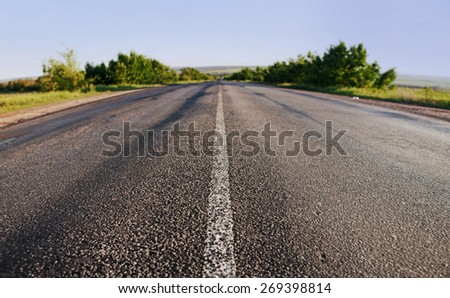 asphalt road through the green field on blue sky in summer day - stock photo