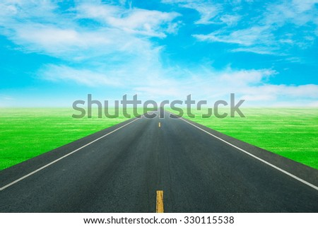 asphalt road through the green field with blue sky - stock photo