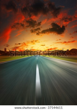 Asphalt road to city under dramatic sunset - stock photo