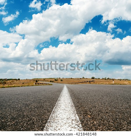 asphalt road to horizon and clouds in blue sky - stock photo