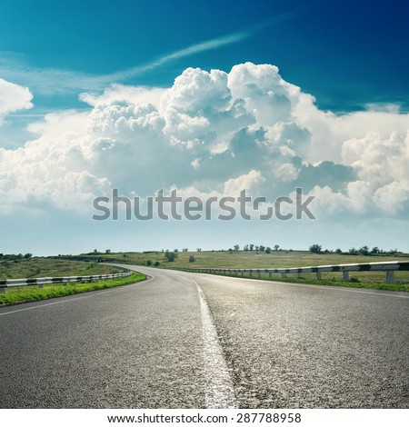 asphalt road to horizon and clouds over it - stock photo