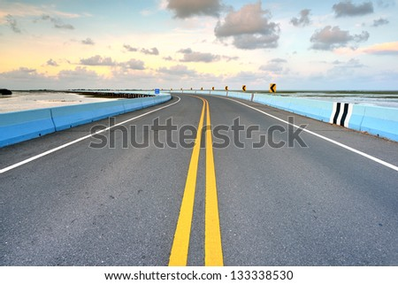 asphalt road to horizon in cloudy sky - stock photo