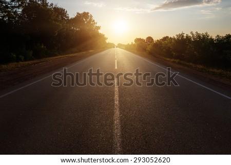 asphalt road to horizon in sunset - stock photo