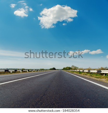 asphalt road to horizon under blue cloudy sky - stock photo