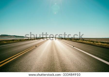 Asphalt road to the horizon line under a burning Sun - stock photo