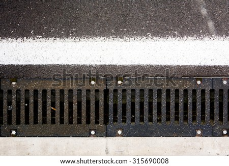 Asphalt road top view background / Texture of an asphalt road / seamless close up / New asphalt texture with white line / Old steel drainage of the asphalt road. - stock photo