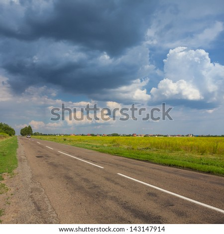 asphalt road under a dense rainy clouds - stock photo