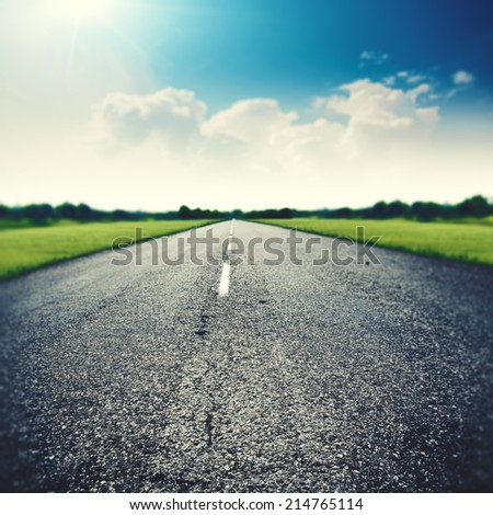 Asphalt road under wide blue skies, abstract travel backgrounds - stock photo