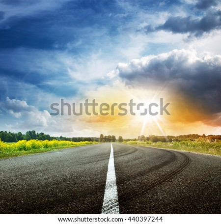 asphalt road view in countryside on sunny summer day with dramatic clouds - stock photo