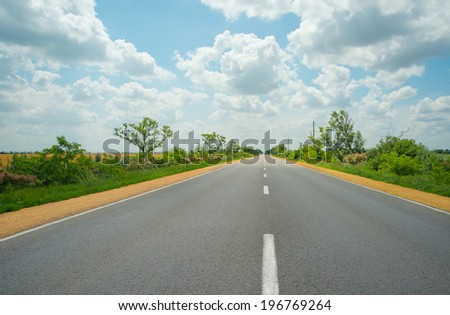 asphalt road. View of rural road and blue cloudy sky