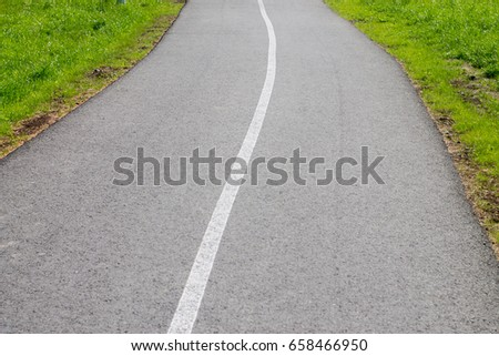 Asphalt road with a separating white stripe. Grass near the road.