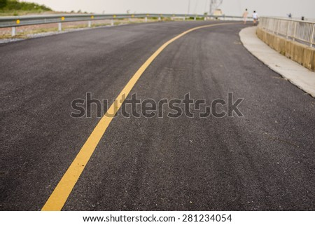 asphalt road with blurry of a small couple walking - stock photo