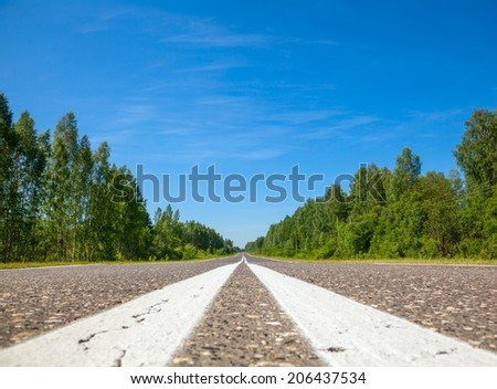 Asphalt road with center lines marking close-up - stock photo