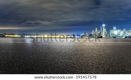 asphalt road with cityscape of seattle at night - stock photo