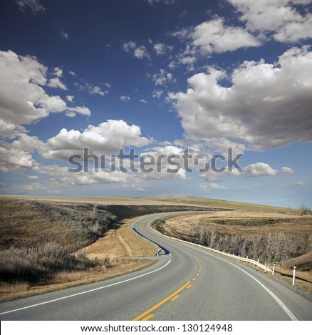 Asphalt road with curves between fields with clouds in the blue sky - stock photo