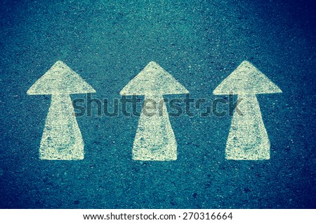 asphalt road with drawn direction arrow - stock photo