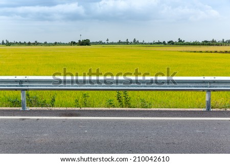Asphalt road with green rice field in Thailand