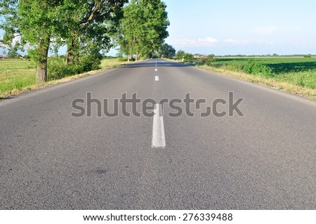 Asphalt road with green trees and blue sky in summer day. Horizontal image - stock photo