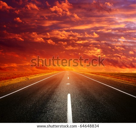 Asphalt road with light on a horizon and clouds - stock photo