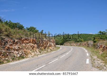 asphalt road with rocky roadside in Provence-Alpes-Cote d'Azur region, France - stock photo