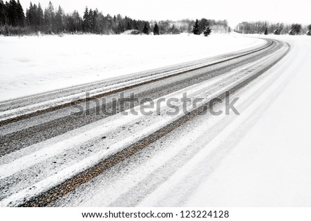 Asphalt road with snow in rural area - stock photo