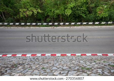 Asphalt road with tree and stone at edge