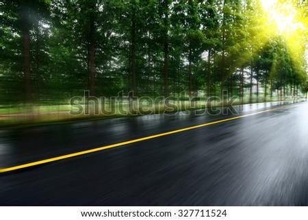 asphalt road with tree lawns under sunshine - stock photo