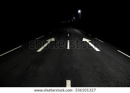 Asphalt road with white arrow signs at night