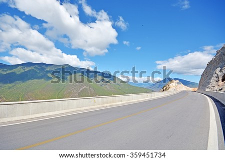 asphalt road with yellow dry field in countryside in summer season  - stock photo