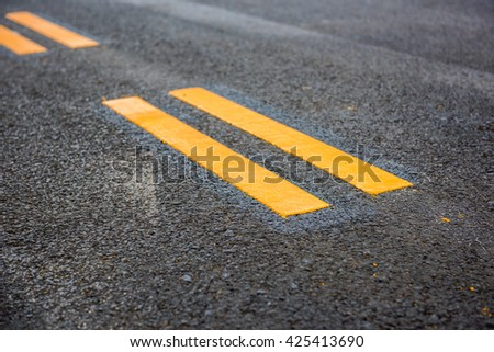 Asphalt road, yellow line on the new road