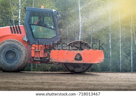 Asphalt roller at work under the bright sunlight, construction of new roads, repair of pavement, lining country roads, modern construction equipment.