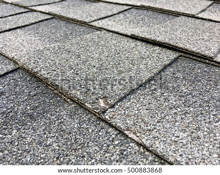 Asphalt shingles with a small bit of a hail damage up close.