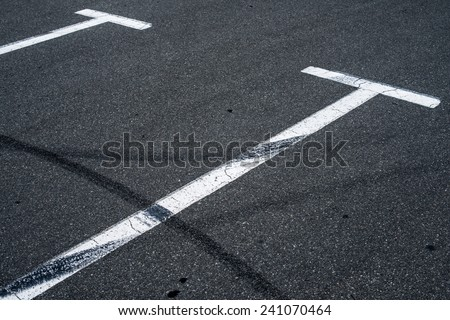 Asphalt surface of the empty parking with white road marking lines and wheel tracks - stock photo