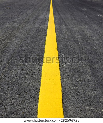 Asphalt surface of the road with a yellow line.