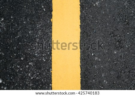 asphalt texture with yellow dashed line,blur and out of focus