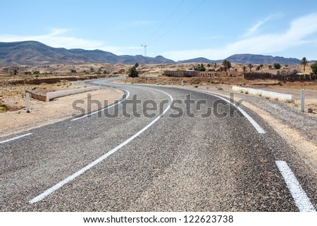 Asphalt way with white road marking in mountain terrain of Africa - stock photo