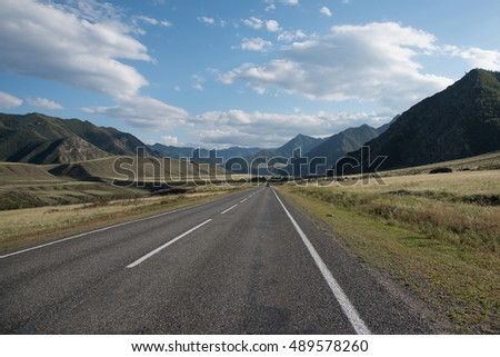 Asphalt winding road in the mountainous area in the summer and blue sky with clouds