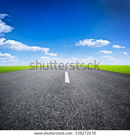 asphalted highway over blue sky with white clouds background - stock photo