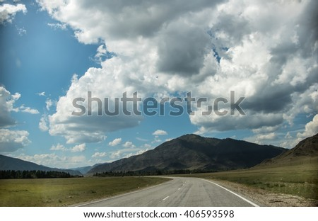 asphalted road leaving in mountains. Green field. Clouds. Blue sky