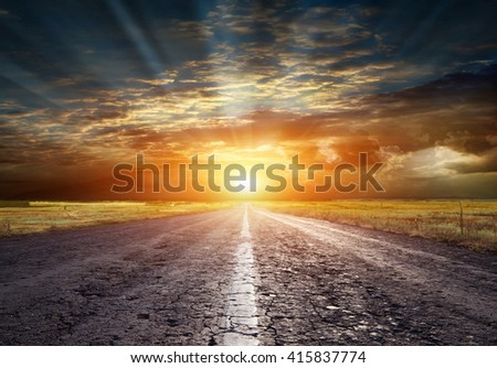 Asphalted road on the background of storm clouds - stock photo