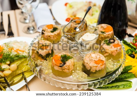 Aspic from meat decorated with parsley on a festive table - stock photo