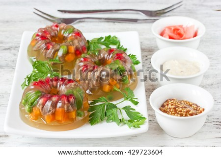 Aspic from meat with green peas, carrot, pomegranate, parsley. Cold appetizer, festive snack meat jelly with vegetables selective focus - stock photo