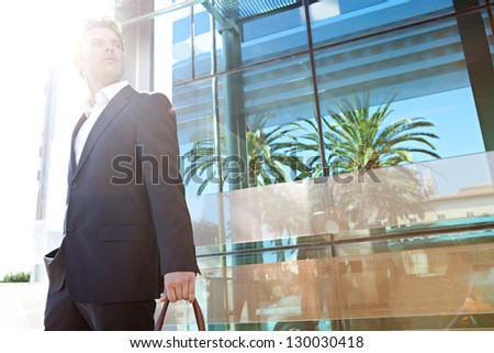 Aspirational fashionable businessman in the city with a reflective modern office building in the background and the sun filtering through his face. - stock photo