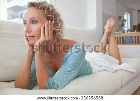 Aspirational home view portrait of an attractive mature healthy woman laying on white sofa at home, thoughtful and relaxing indoors. Home living and well being lifestyle. - stock photo