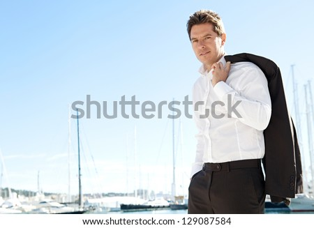 Aspirational successful businessman standing by luxury boats and yachts against a deep blue sky, holding his jacket over his shoulder. - stock photo