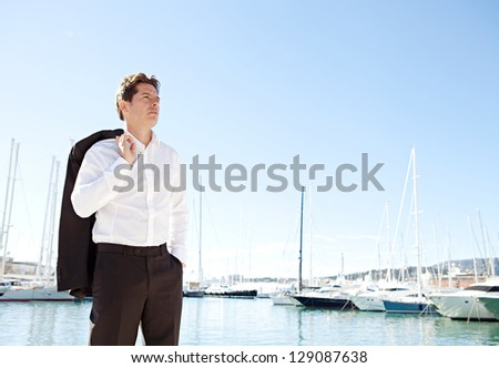 Aspirational successful businessman standing by luxury boats and yachts in a coastal city against a deep blue sky on a sunny day. - stock photo